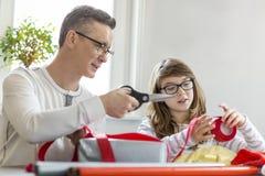 在家包裹圣诞节礼物的父亲和女儿 免版税库存图片
