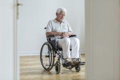 在家单独坐的轮椅的哀伤的被麻痹的老人 图库摄影