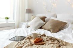 在家压片个人计算机、咖啡杯和新月形面包在床上 免版税库存图片