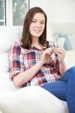 在家发正文消息的十几岁的女孩从手机 免版税库存照片