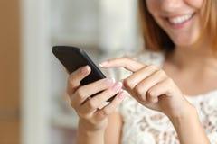 在家发短信在一个巧妙的电话的妇女 免版税库存照片
