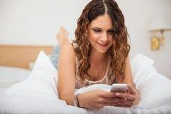 在家发短信逗人喜爱的女孩 库存照片