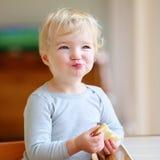 在家吃三明治的滑稽的小女孩 图库摄影