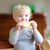 在家吃三明治的滑稽的小女孩 库存照片