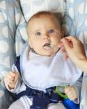 在家吃与匙子的女婴 免版税库存图片