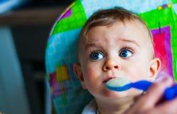 在家吃与匙子的男婴 免版税库存图片