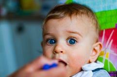 在家吃与匙子的男婴 库存照片