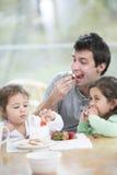 在家吃与打好的奶油的父亲和女儿草莓 图库摄影
