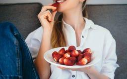 在家吃健康食物srawberries的少妇,健康cle 免版税库存图片