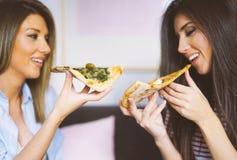 在家吃切片鲜美意大利比萨-愉快的俏丽的夫人的年轻美女一起享受一顿快的膳食 图库摄影