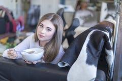 在家吃在沙发的年轻女人酸奶 免版税图库摄影