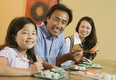 在家吃寿司的家庭 库存图片