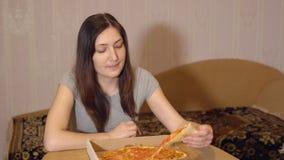 在家吃开胃薄饼的深色的妇女 免版税图库摄影
