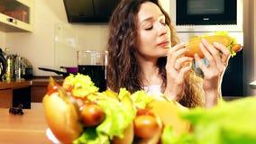 在家吃热狗和喝可乐的美丽的深色的少妇 背景汉堡干酪鸡概念黄瓜深鱼食物油煎了旧货莴苣木三明治的蕃茄 免版税库存图片