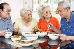 在家吃膳食的高级中国朋友 免版税库存照片