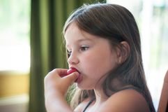 在家吃草莓莓果的小女孩在一张桌上在一个夏日 免版税库存图片