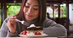 在家吃蛋糕的愉快的亚裔妇女 免版税图库摄影
