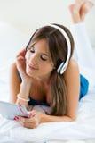 在家听到与片剂的音乐的美丽的女孩在沙发 库存图片