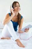 在家听到与片剂的音乐的美丽的女孩在沙发 免版税图库摄影