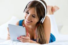 在家听到与片剂的音乐的美丽的女孩在沙发 库存照片