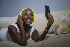 在家听到与耳机和手机沙发长沙发的音乐的年轻愉快和美丽的轻松的黑人美国黑人的妇女 免版税库存照片