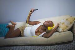 在家听到与耳机和手机沙发长沙发的音乐的年轻愉快和美丽的轻松的黑人美国黑人的妇女 免版税图库摄影