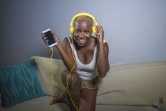 在家听到与耳机和手机沙发长沙发的音乐的年轻愉快和美丽的轻松的黑人美国黑人的妇女 库存图片