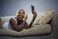 在家听到与耳机和手机沙发长沙发的音乐的年轻愉快和美丽的轻松的黑人美国黑人的妇女 图库摄影