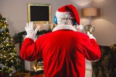 在家听到在耳机的音乐的圣诞老人在圣诞节时间 免版税库存照片