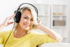 在家听到音乐的年轻和美丽的十几岁的女孩 免版税库存图片