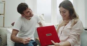 在家吸引人年轻夫妇,舒适大气,庆祝某事,给他的妇女的一件礼物她的人是非常 股票录像