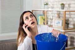 在家告诉的妇女水漏出的水管工 免版税库存图片