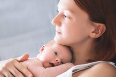 在家哺乳新出生的婴孩的母亲 图库摄影