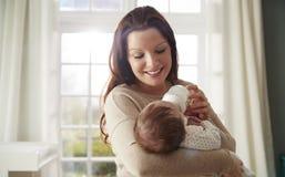 在家喂养从瓶的母亲新出生的婴孩 免版税图库摄影