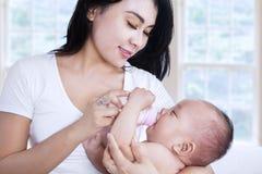 在家喂养她的婴孩的亚裔母亲 免版税库存图片