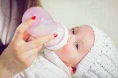 在家喂养他们新的女婴的年轻母亲 免版税库存照片
