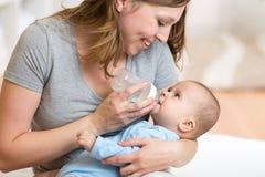 在家喂养有牛奶瓶的逗人喜爱的母亲婴孩 库存照片