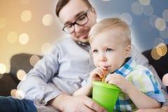 在家喝从杯子的父亲和儿子 免版税库存图片