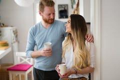 在家喝咖啡和微笑的爱的浪漫夫妇 库存照片