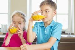 在家喝橙汁的兄弟姐妹在厨房里 免版税库存图片