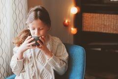 在家喝热的可可粉的孩子女孩在冬天周末,坐舒适椅子 免版税图库摄影
