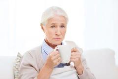 在家喝热的茶的病的资深妇女 免版税库存照片