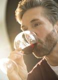 在家喝红葡萄酒的人 免版税图库摄影