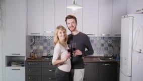 在家喝红葡萄酒的年轻夫妇在厨房里 免版税库存照片