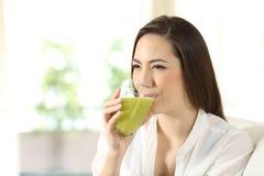 在家喝绿色蔬菜汁的妇女 免版税库存照片