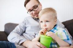 在家喝从杯子的父亲和儿子 免版税库存照片