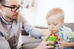 在家喝从杯子的父亲和儿子 库存图片