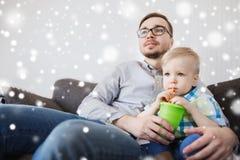 在家喝从杯子的父亲和小儿子 免版税库存照片