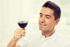 在家喝从玻璃的愉快的人红葡萄酒 免版税库存照片