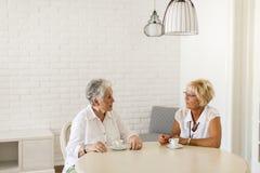 在家喝coffe和谈话的两个老妇人 库存照片